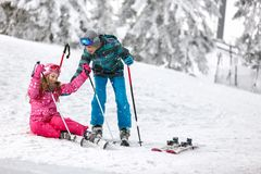 Brother helps his sister to get up from ski terrain with skis Royalty Free Stock Photo