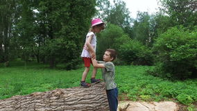 Brother helps sister. Boy teenager drags the the girl child with wooden logs on the ground. stock footage