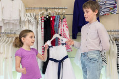 The brother helps sister to choose clothes. In shop of childrens clothing stock image