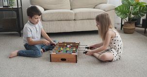 Children playing foosball at home. Brother with her sister playing foosball at home stock footage