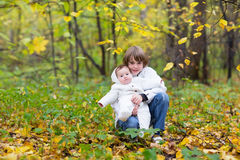 Brother holding his baby sister in an autumn park with yellow trees. Brother holding his baby sister both in white jackets in an autumn park with yellow trees Royalty Free Stock Photography