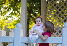 Brother holding his baby sister on a white wooden deck. On sunny day Stock Photography