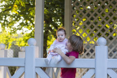 Brother holding his baby sister on a white wooden deck. On sunny day Royalty Free Stock Photos