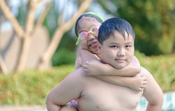 Brother holding his sister on his back in swimming pool royalty free stock photography