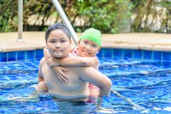 Brother holding sister on his back in swimming pool stock images
