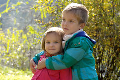 Brother hugging sister in autumn park Stock Image
