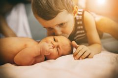 Brother kissing little newborn sister royalty free stock photo