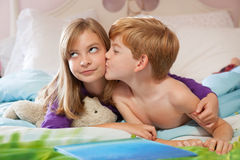 Brother kissing sister on cheek. Royalty Free Stock Image