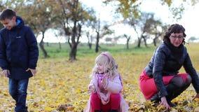 Brother, la hermana y la madre están jugando con las hojas de arce amarillas del otoño almacen de metraje de vídeo