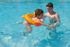 Swimming lesson. Brother is learning his sister to swim Royalty Free Stock Image