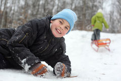 Brother lie on snow, sister pulls sleigh Stock Images