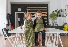 Brother and little sister, sitting on a big white table in creative studio. royalty free stock photography