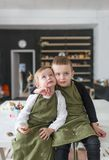 Brother and little sister, sitting on a big white table in creative studio. royalty free stock photo