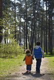 Brother and little sister are on the road in the woods. Stock Images