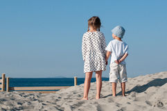 Brother looking at his older sister. The back view of the standing on a beach two kids looking to the sea stock photo