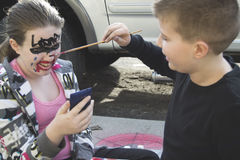 Brother painting sisters face Stock Image