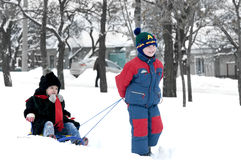 Brother pulling sister on sledge Royalty Free Stock Photo