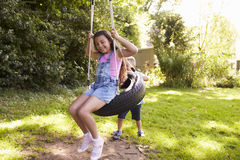 Brother Pushing Sister On Tire Swing In Garden Royalty Free Stock Photo