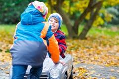 Brother que empuja el coche para el niño Felicidad, diversión, ocio en parque de la caída Fotografía de archivo