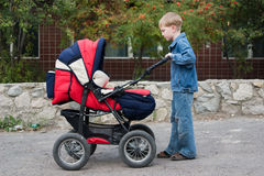 The brother rolls the baby. The brother rolls the younger sister in a pram Royalty Free Stock Photography
