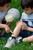 Brothers help. Two kids, one of them is injured and the other is helping him Royalty Free Stock Photo