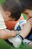 Brothers help about shoelace. Kid helping his brother about tying his shoe laces Royalty Free Stock Photo
