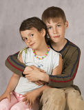 Brother's hugs. Brother hug a Sister Sitting On Couch Royalty Free Stock Photography