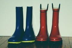 Brother`s Rainboots on Hardwood Floor royalty free stock photo