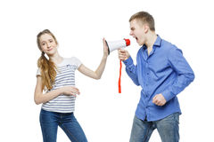 Brother screaming at sister. Teen age boy screaming at girl through megaphone. Brother and sister isolated on white background. Copy space Royalty Free Stock Image