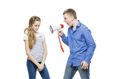 Brother screaming at sister. Teen age boy screaming at girl through megaphone. Brother and sister isolated on white background. Copy space Stock Photography