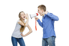 Brother screaming at sister. Teen age boy screaming at girl through megaphone. Brother and sister isolated on white background. Copy space Stock Photos