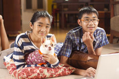Brother and sis. Brother, sister and a dog playing notebook on floor Stock Photos