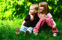 Brother and sister. Two children sitting in park together Stock Images