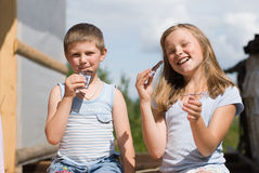 The brother and sister. On summer vacations eat chocolate.  A warm sunny day in village Stock Photo