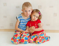 The brother and sister. The boy and the girl sit on a floor having embraced Royalty Free Stock Image