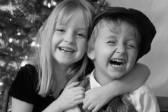 Brother and Sister. Laughing in front of the Christmas tree Stock Photography