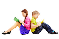 Brother and sister. Portrait of brother and sister sitting back to back and reading books Royalty Free Stock Images