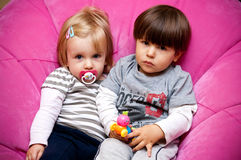 Brother and sister. A young brother and sister with serious expressions sit side by side on a pink chair Stock Photos