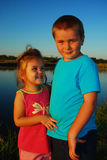 Brother and sister. Funny laughing girl looking at her beloved brother which is staring at camera outside at a pond Royalty Free Stock Photo