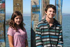 Brother and Sister. Two kids standing in front of a fence at the end of a pier Stock Images