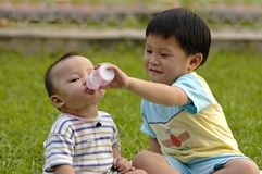 Brother & Sister. Edmond sharing his yogurt drink with her sister Eloise Royalty Free Stock Images