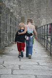 Brother & Sister. Brother and Sister walking together arm in arm as friends royalty free stock photo