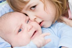 Brother and sister. Cute girl kissing her little brother, close up Stock Photo