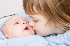 Brother and sister. Cute girl kissing her little brother, close up Royalty Free Stock Photos