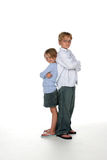 Brother and sister. Standing back to back with their arms crossed Royalty Free Stock Image