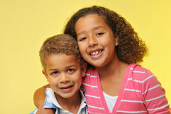Brother and sister. Smiling isolated on yellow Royalty Free Stock Photos