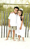 Brother and Sister. A Brother and sister standing in the sand dressed in white Stock Photography