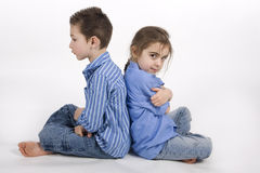 Brother and sister. 7 year old boy and his 5 year old sister sitting back to back Stock Photos
