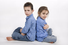 Brother and sister. 7 year old boy and his 5 year old sister sitting back to back Stock Photography