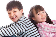 Brother and sister. Sitting back to back isolated over white Royalty Free Stock Photos